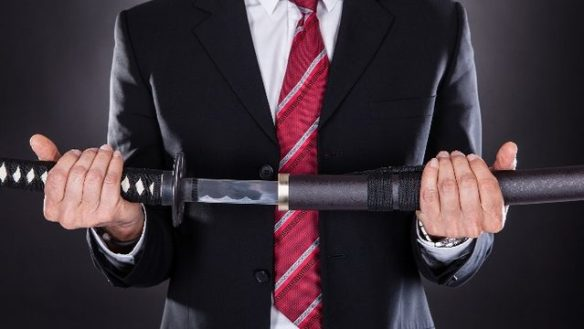 A man in business attire holding a Japanese sword